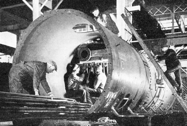 ERECTING THE SUPERHEATER in the boiler of a mammoth American freight locomotive