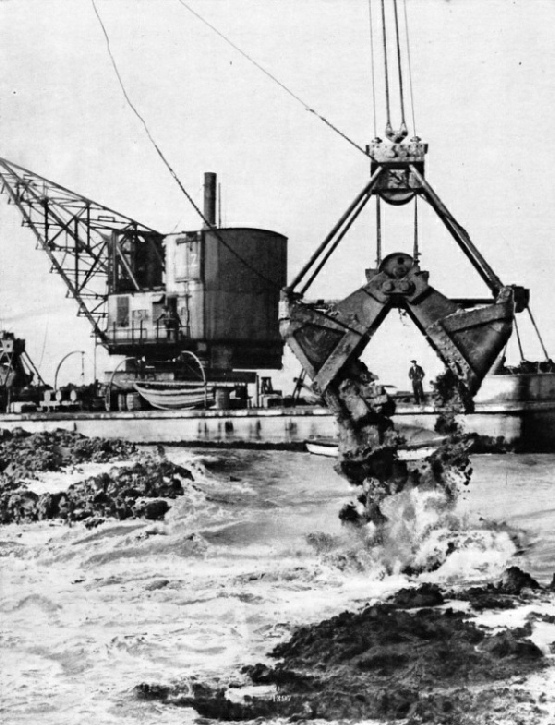 ENORMOUS GRABS, operated by floating cranes, were used to build up the core of the dam