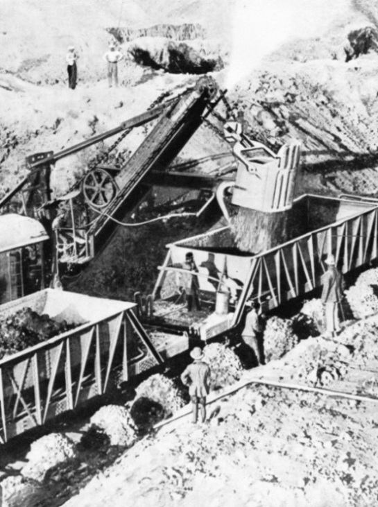 Steam shovels load copper ore into railway trucks